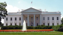A picture of the white house with flowers and a fountain