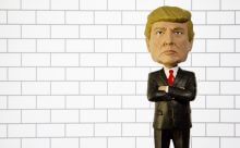 Donald Trump Bobble Head figure standing in front of a wall.