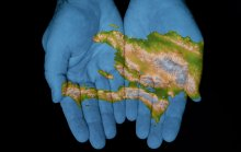 an image of Haiti in a pair of blue hands: temporary protected status was given to Haiti