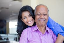 new 601 a Unlawful Presence Waiver...Closeup portrait family young woman in blue shirt holding older man in pink collar button down from behind happy isolated indoors home background