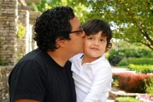 A Hispanic father gives a kiss to he young son: extreme hardship, 601 a visa