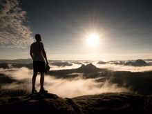 Man at the top of a mountain looking the misty landscape around. How humility is your best business assett