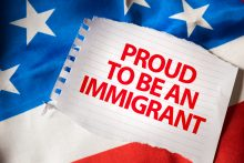 A message on a piece of paper that lies on the American Flag that says, proud to be an immigrant. Mexican immigrants