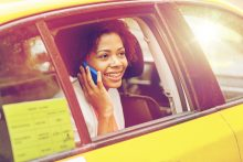 Immigrant entrepreneur black woman in a car talking on her cell phone